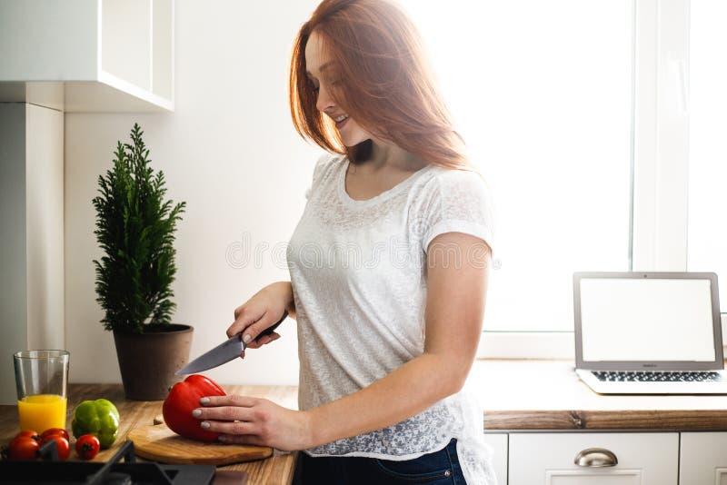 Nettes Mädchen bereitet einen Gemüsesalat, schneidet roten Pfeffer zu Sind in der Nähe Tomaten und grüne Paprikas stockfotos