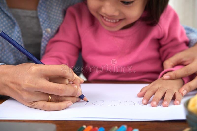 Nettes Mädchen, das Alphabet mit Mutter lernt stockbilder
