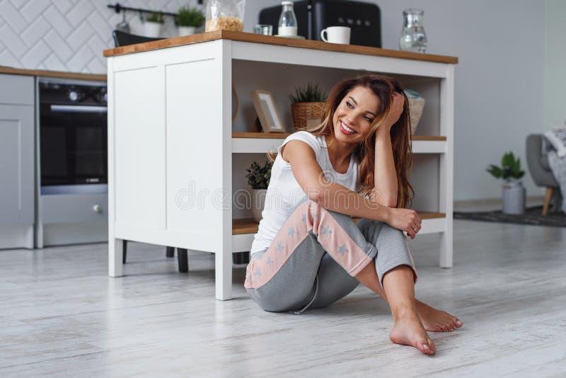 Nettes M?dchen, das auf dem Boden auf dem Hintergrund der stilvollen K?che sitzt Hausarbeitkonzept der Frauen lizenzfreie stockbilder