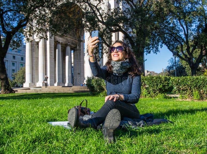 Nettes Mädchen, das auf dem grünen Gras nimmt ein selfie und ein Lächeln sitzt lizenzfreie stockfotografie