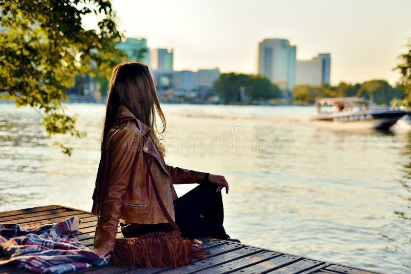 Nettes Mädchen, das auf dem Pier im Fall bei Sonnenuntergang sitzt stockbild