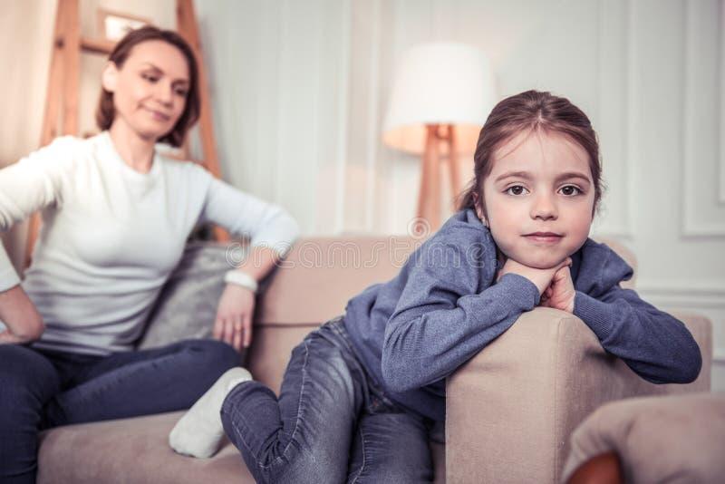 Nettes nettes Mädchen, das auf dem Sofa sitzt stockfoto