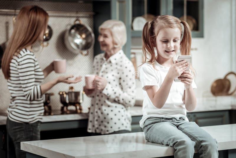 Nettes Mädchen, das auf dem Tisch mit Gerät während ihre Verwandtunterhaltung sitzt lizenzfreies stockfoto