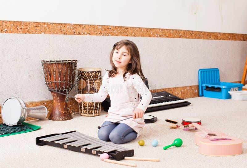 Nettes Mädchen, das auf dem Xylophon spielt lizenzfreies stockfoto