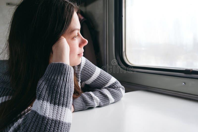 Nettes Mädchen, das auf einem Zug sitzt und aus dem Fenster heraus schaut stockfotos