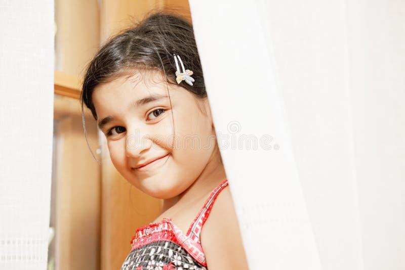 Nettes Mädchen, das aus Trennvorhängen heraus schaut lizenzfreie stockfotografie
