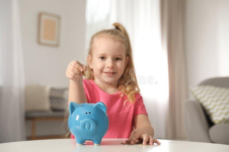 Nettes Mädchen, das bei Tisch Münze in Sparschwein setzt Stecken eines Geldes in eine piggy Querneigung stockfoto