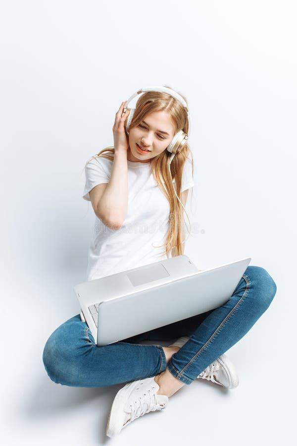 Nettes Mädchen, das an Computer arbeitet und Musik, lokalisiert auf weißem Hintergrund, glücklich und nett hört lizenzfreies stockfoto