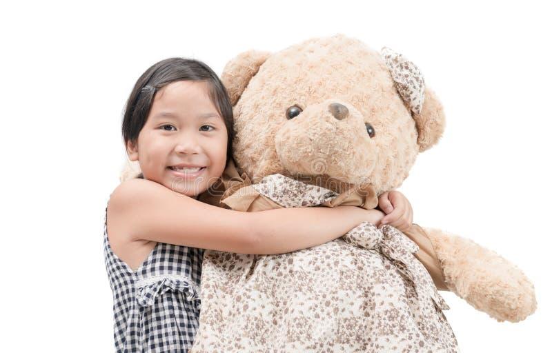 Nettes Mädchen, das den großen Teddybären lokalisiert umarmt stockfoto