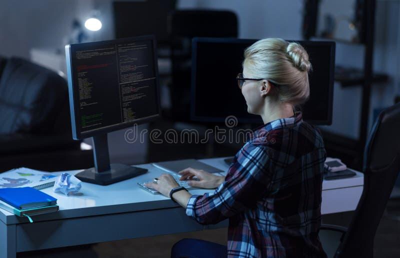 Nettes IT-Mädchen, das in der Dunkelheit arbeitet, beleuchtete Raum stockfoto