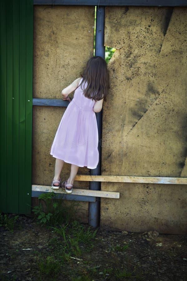 Nettes Mädchen, das durch Loch in der Wand schaut stockfotografie
