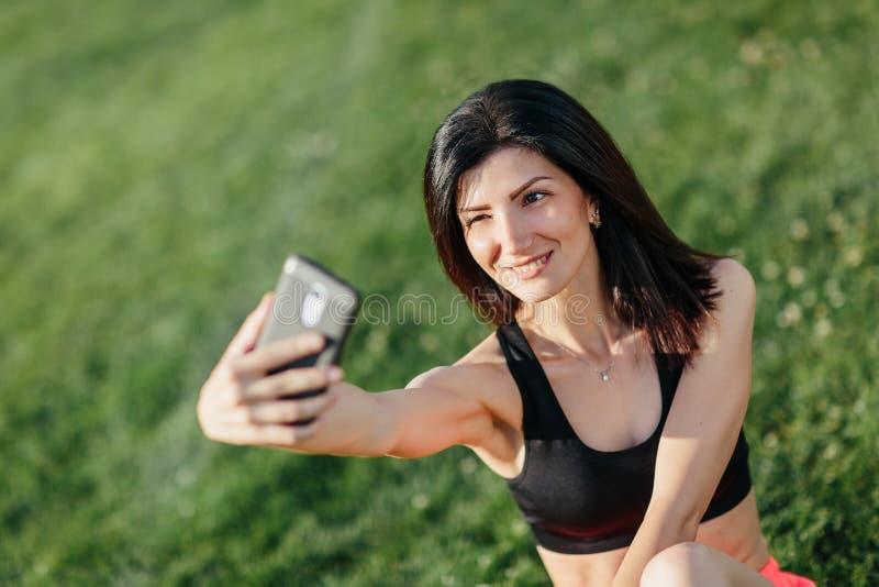 Nettes Mädchen, das ein selfie mit ihrem Telefon nimmt, während sie etwas Yoga an einem Park tun lizenzfreie stockbilder