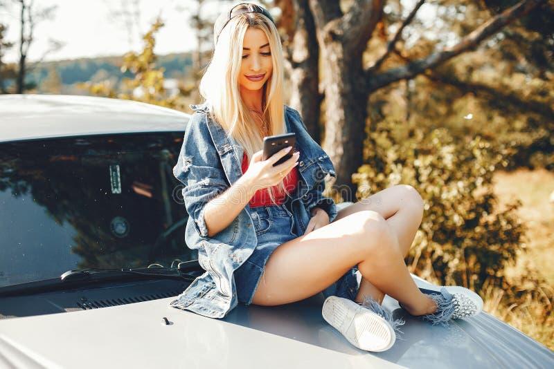 Nettes Mädchen, das in einem Sommerpark sitzt lizenzfreies stockbild