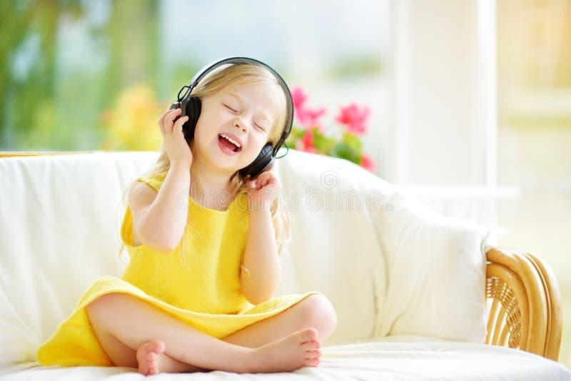 Nettes Mädchen, das enorme drahtlose Kopfhörer trägt Hübsches Kind, das Musik hört Schulmädchen, das den Spaß hört auf Kind-` s L stockbild