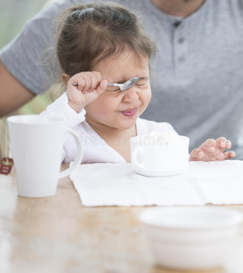 Nettes Mädchen, das Gesicht beim Haben der Creme mit Vater zu Hause macht lizenzfreies stockfoto