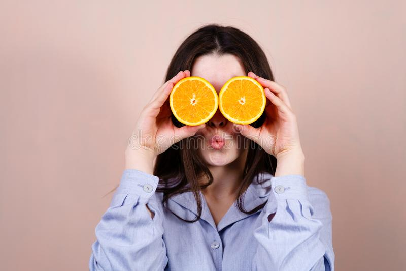 Nettes Mädchen, das Hälften der Orange nahe Gesicht hält lizenzfreies stockfoto