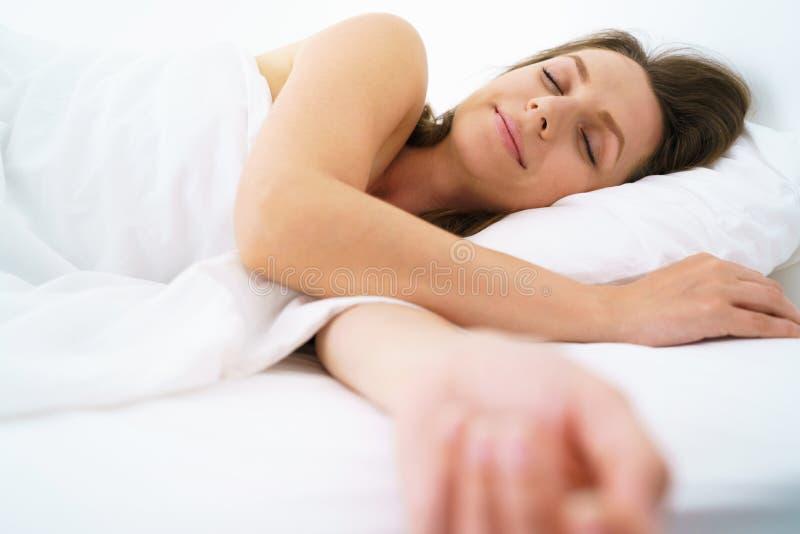 Nettes Mädchen, das im Bett schläft und an der Kamera lächelt stockbild