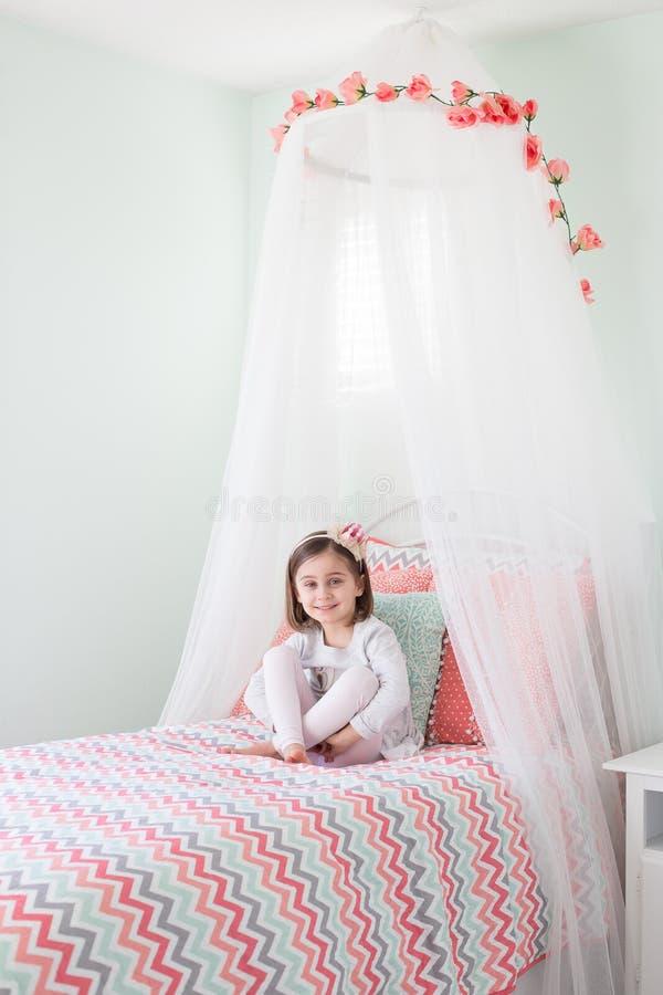 Nettes Mädchen, das im Bett sitzt stockbilder