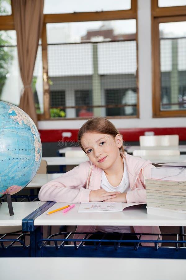 Nettes Mädchen, das mit Büchern und Kugel am Schreibtisch sitzt lizenzfreie stockbilder
