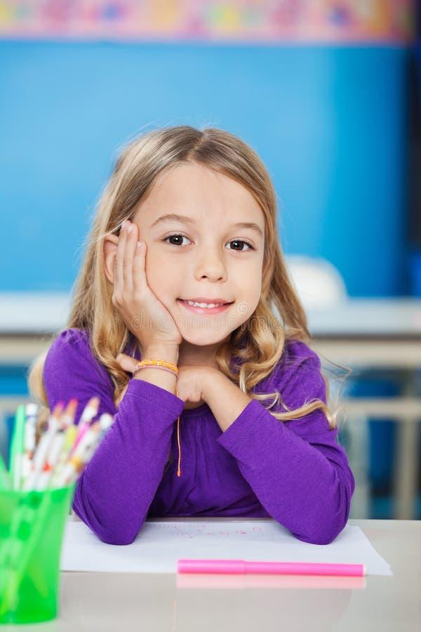 Nettes Mädchen, das mit der Hand auf Chin At Desk sitzt lizenzfreies stockfoto