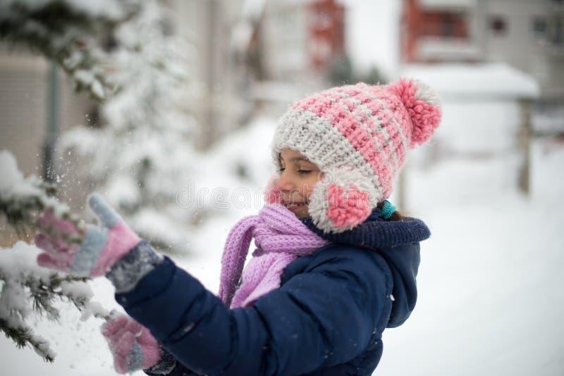 Nettes Mädchen, das mit Schnee spielt stockfotos
