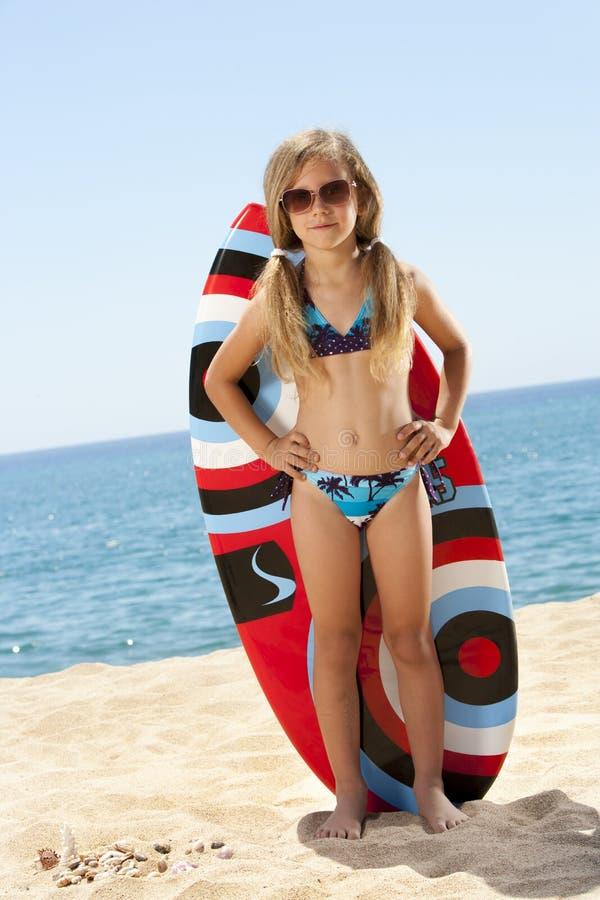 Nettes Mädchen, das mit Surfbrett auf Strand steht. lizenzfreies stockfoto