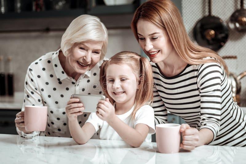 Nettes Mädchen, das modernen Smartphone hält und selfies mit Familie nimmt stockfotos