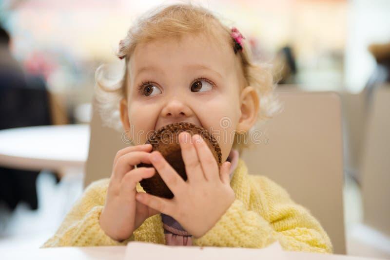Nettes Mädchen, das Muffins im Café isst stockfotos