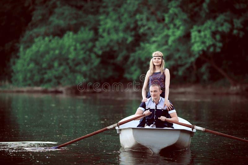 Nettes Mädchen, das nahen Rudersportkerl auf Boot bleibt lizenzfreies stockfoto
