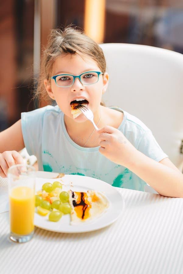 Nettes Mädchen, das Pfannkuchen, frische Früchte isst und Orangensaft während Frühstück gesunden Lebensstils, Pflanzenkost trinkt stockfotos
