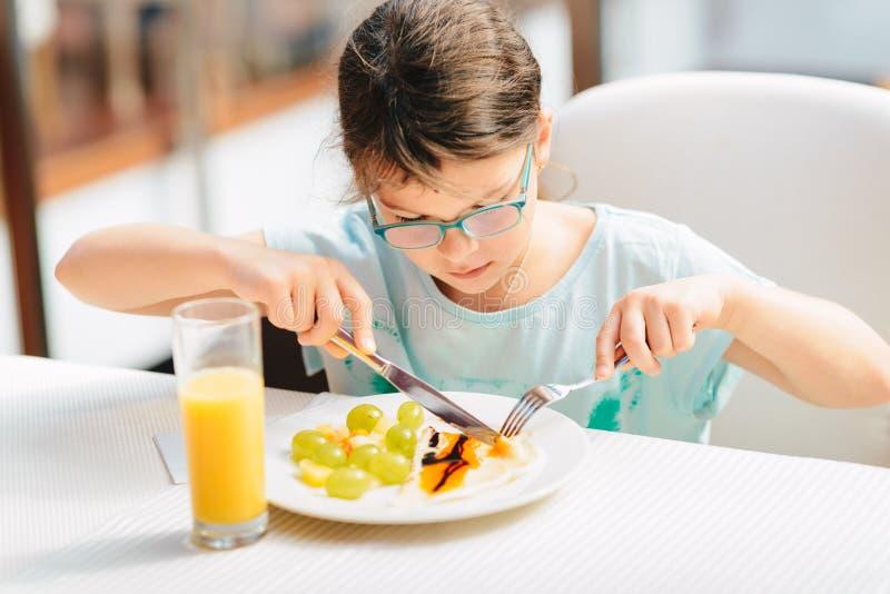 Nettes Mädchen, das Pfannkuchen, frische Früchte isst und Orangensaft während Frühstück gesunden Lebensstils, Pflanzenkost trinkt lizenzfreie stockfotografie