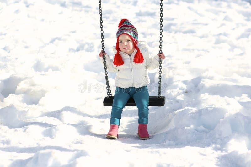 Nettes Mädchen, das Spielplatz am Winter genießt stockfotografie