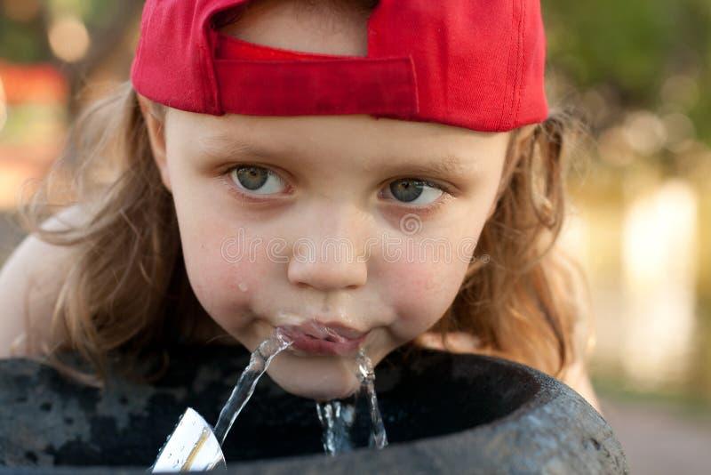 Nettes Mädchen, das von einem Wasserbrunnen trinkt stockfotos