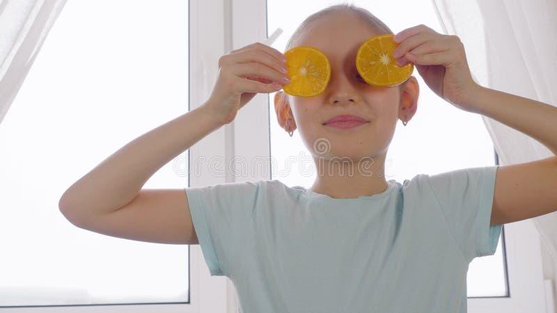 Nettes Mädchen, das vordere Augen der orange Scheiben auf Küchenfensterhintergrund hält stockbild