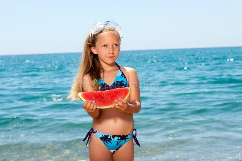 Nettes Mädchen, das Wassermelone auf Strand isst. stockbilder