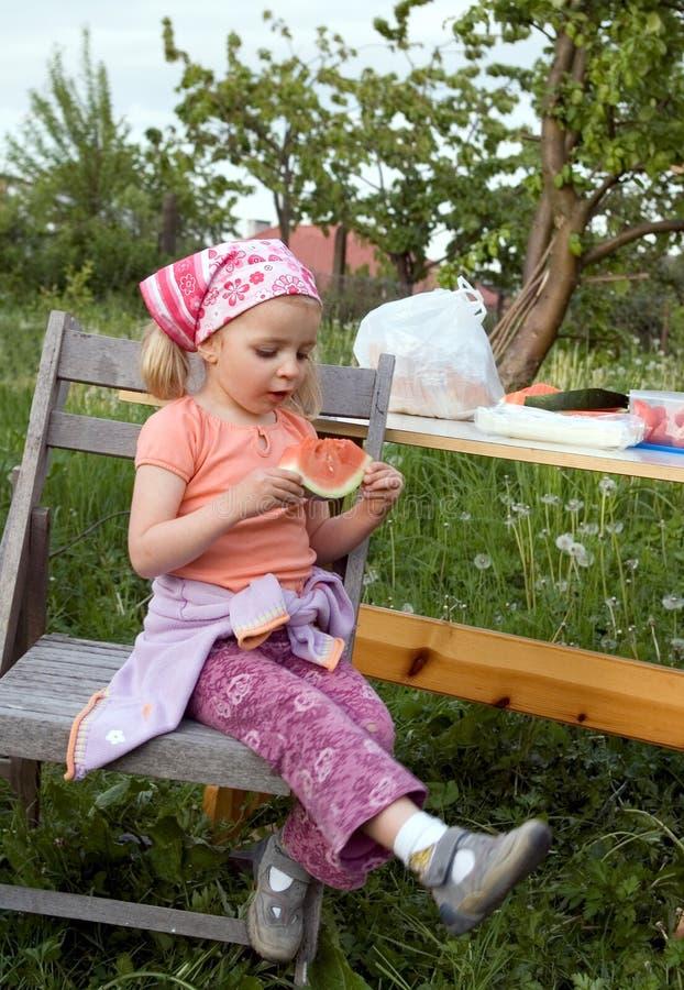Nettes Mädchen, das Wassermelone isst stockbild