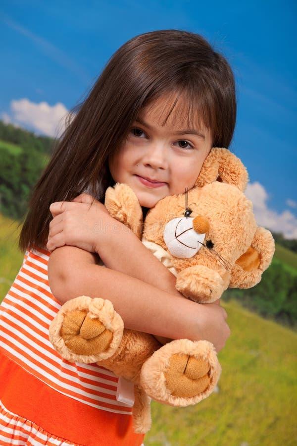 Nettes Mädchen, das weiches Spielzeug anhält stockfotos