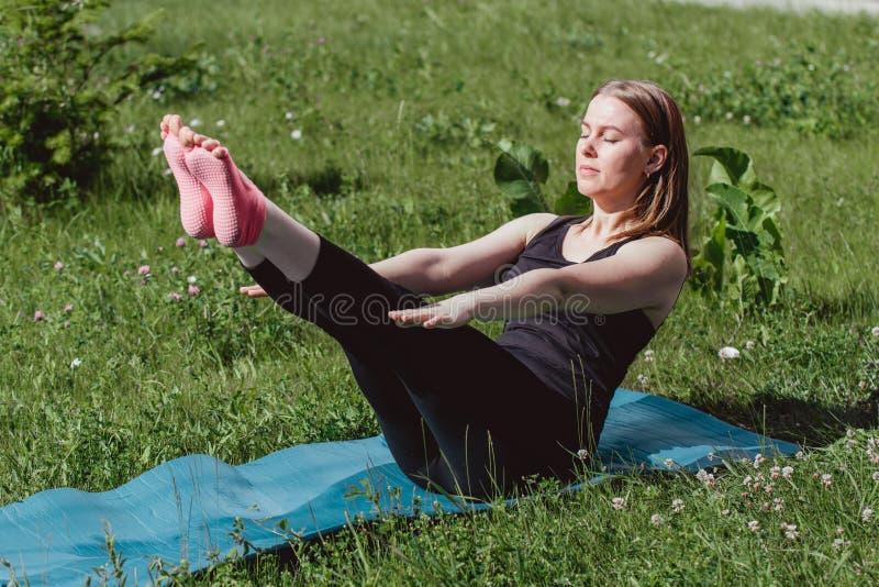 Nettes M?dchen in der schwarzen Kleidung auf dem gr?nen Gras, das Yoga tut Tr?gt Lebensstil zur Schau stockbilder