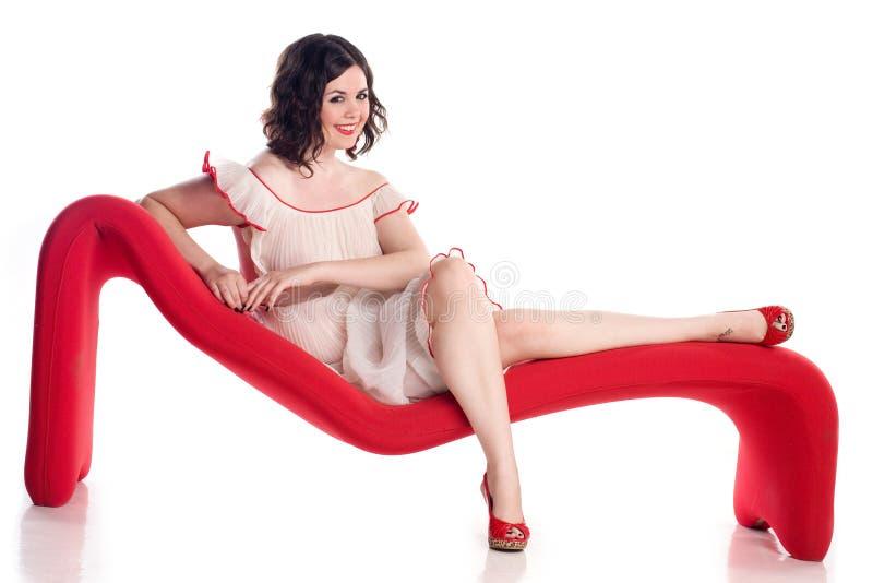 Nettes Mädchen in der Stift-oben Haltung auf roter Couch stockfotografie