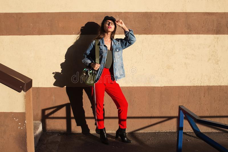 Nettes Mädchen des jungen hübschen Hippies, das auf der Straße am sonnigen Tag, Spaß allein, stilvolle Kleidung und Gläser habend stockbilder