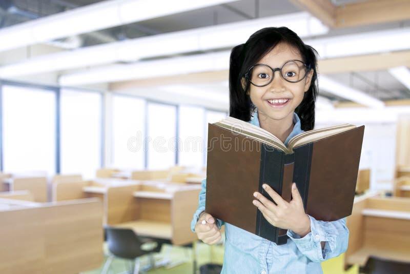 Nettes Mädchen hält Buch im Klassenzimmer lizenzfreies stockfoto