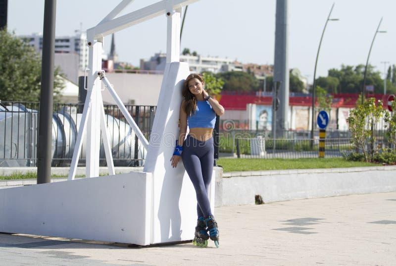 Nettes Mädchen, hübsch, Sitz sportlich, Haltungen, Inline-Rochen auf Basketballplatz stockfotografie