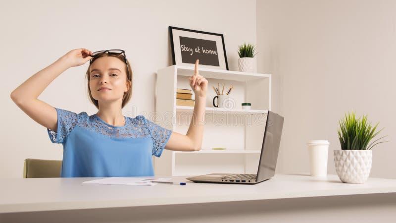 Nettes Mädchen im Büro zeigt einen Finger zum Aufschriftaufenthalt zu Hause lizenzfreies stockbild