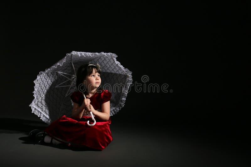Nettes Mädchen im roten Kleid mit weißem Sonnenschirm stockbilder