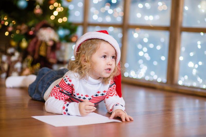 Nettes Mädchen im roten Weihnachtshut einen Brief schreibend Santa Claus lizenzfreies stockbild