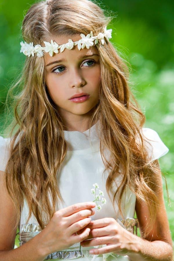 Nettes Mädchen im weißen Kleid, das Blume hält. stockfoto
