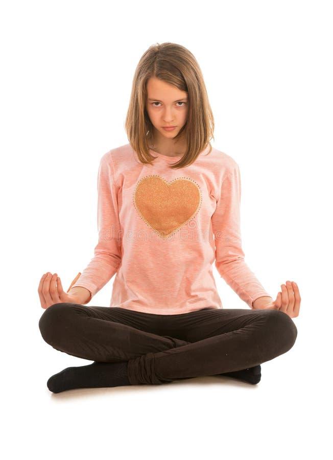 Nettes Mädchen meditiert beim Sitzen im Lotussitz stockfoto