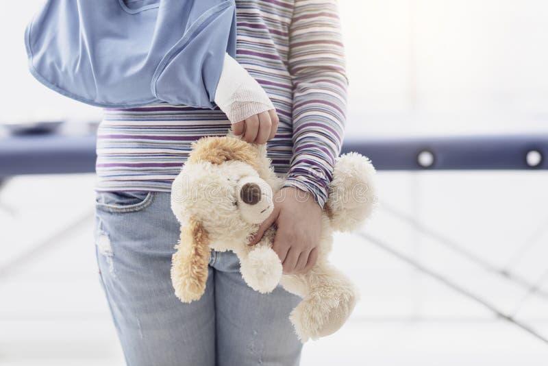 Nettes Mädchen mit Armklammer und Teddybär stockfotos