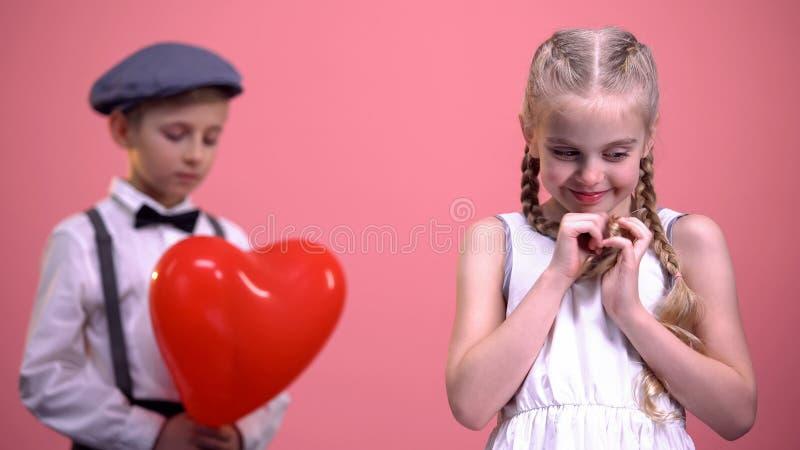 Nettes Mädchen mit Borten lächelnd zur Kamera mit schüchternem Jungen im Hintergrund, erste Liebe lizenzfreies stockfoto