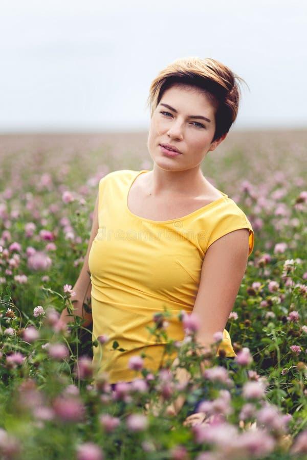 Nettes Mädchen mit dem kurzen Haar, welches das Sitzen auf dem Blumengebiet aufwirft lizenzfreie stockbilder
